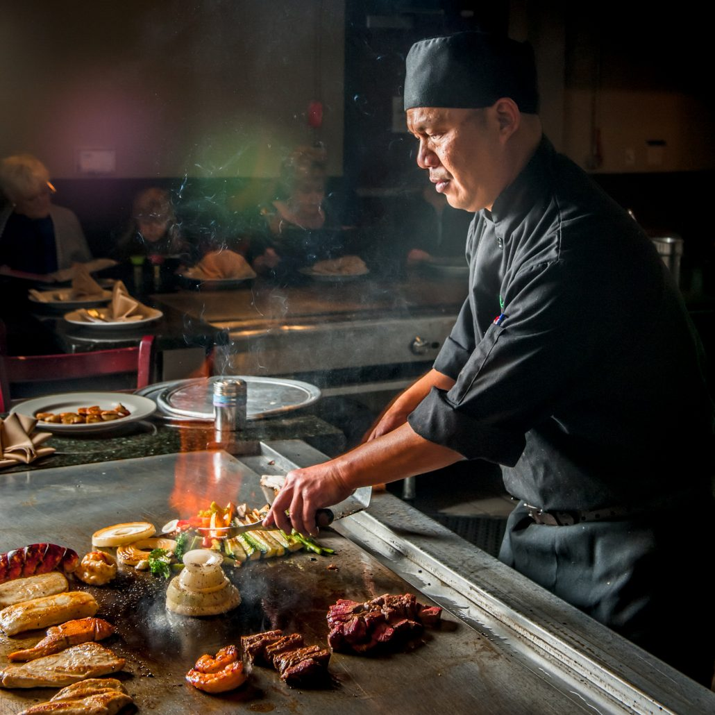 4445e60c25c1 Japanese teppan yaki master chef at the grill with meat and veggies