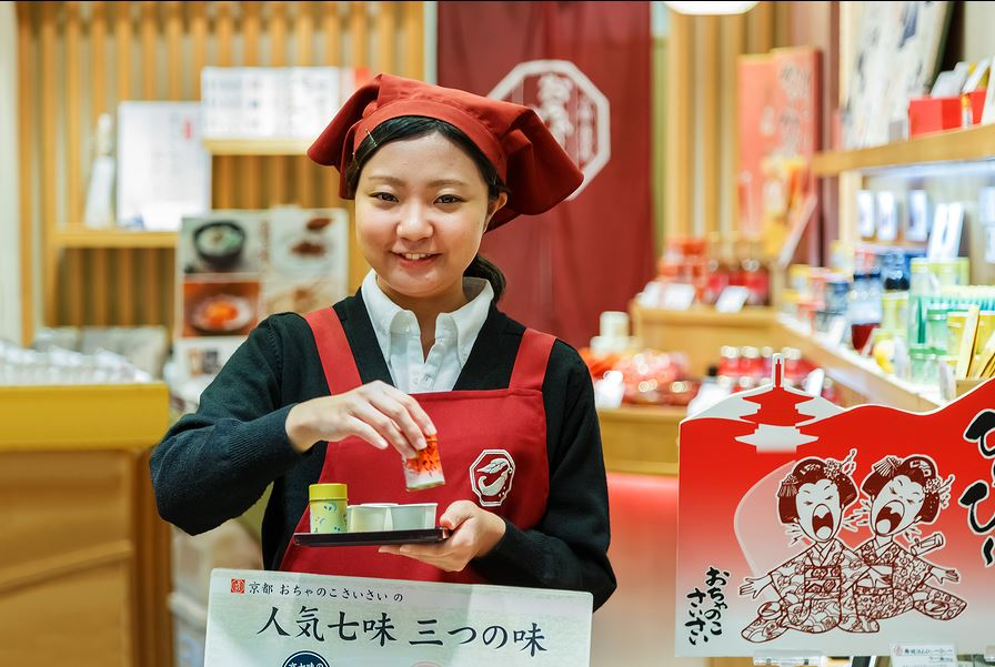 Kyoto shopkeeper preparing food samples for her customers