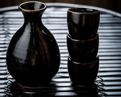 Tasty sake in black ceramics or tokkuri on black table
