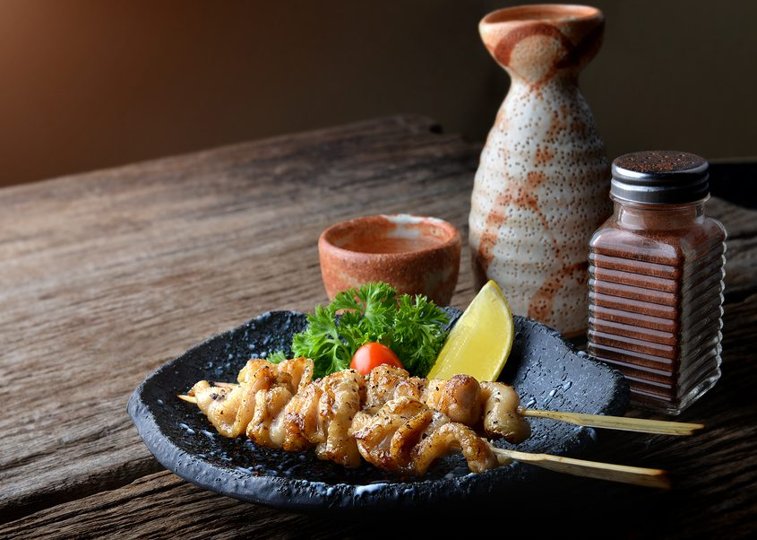 Chicken skin grilled with charcoal fire in Japanese style call torikawa or yakitori serve in izakaya food restaurant.