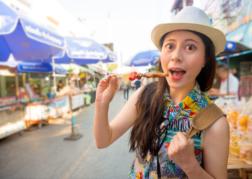 young girl traveler enjoying delicious grilled yakitori chicken skewers on street market in Japan